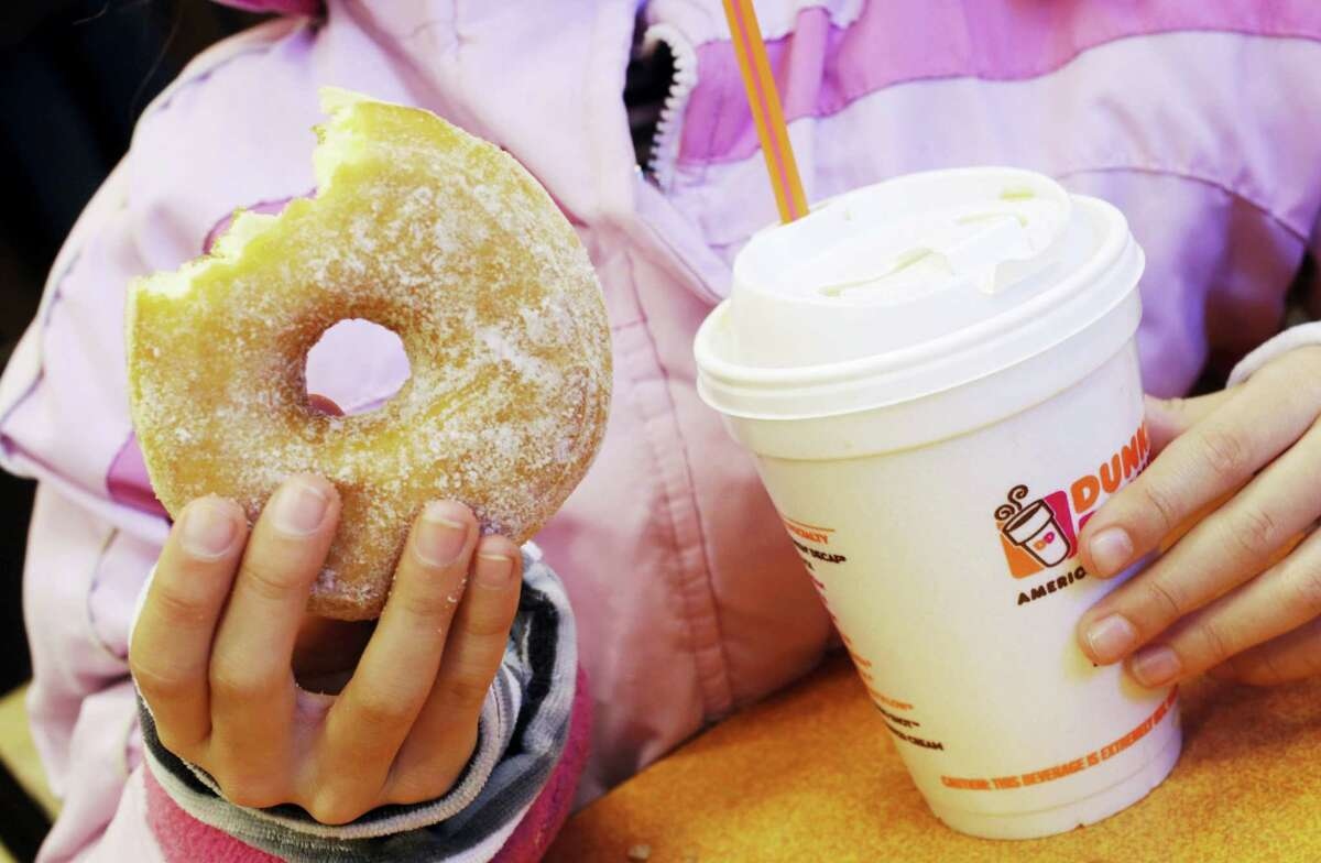 In this Feb. 14, 2013 photo, a girl has a doughnut and a beverage at a Dunkin' Donuts in New York.