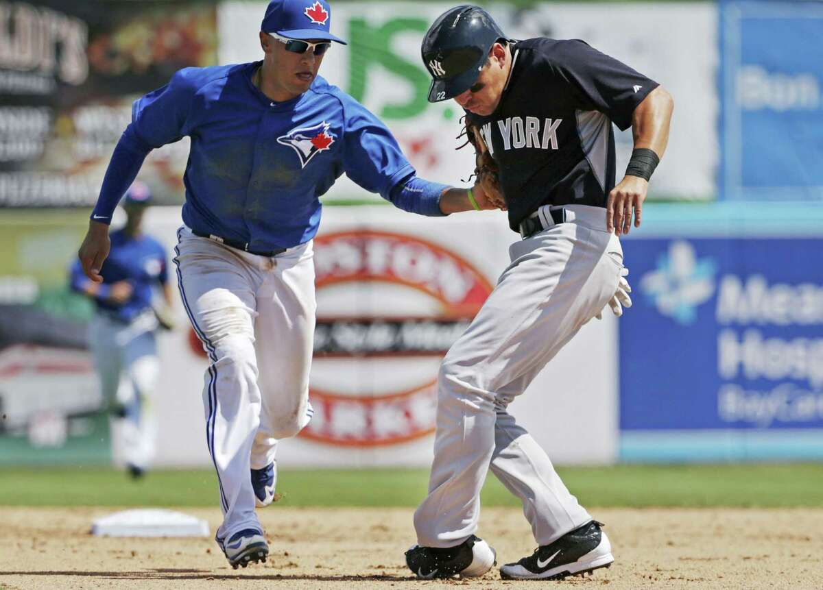 Toronto Blue Jays second baseman Ryan Goins, left, tags New York Yankees outfielder Jacoby Ellsbury during a game earlier this spring.