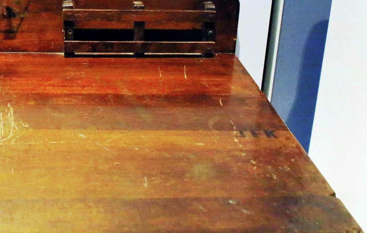 """In this Nov. 5, 2015 photo, a detail shows the initials """"JFK,"""" right, on a desk displayed in the exhibit titled """"Young Jack"""" at the John F. Kennedy Presidential Library and Museum in Boston."""