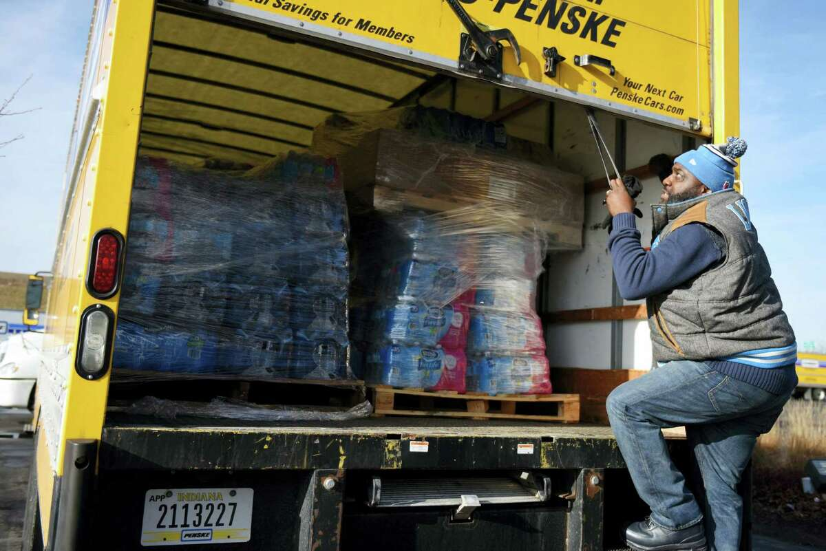 Dwayne Maton, of Detroit, closes a truck's door that is filled with water for Flint, Mich. on Feb. 1, 2016. Metro Detroit and Flint churches are working together to deliver cases of water after river water was not treated properly and lead from pipes leached into Flint homes.