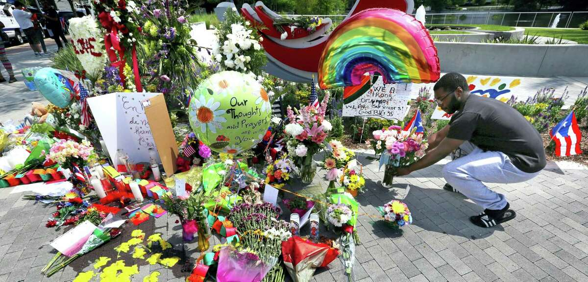 C.J. Ford of Orlando places flowers as visitors continue to pay their respects at a makeshift memorial at Orlando Regional Medical Center, a few blocks from the Pulse nightclub in Orlando, Fla., Tuesday, June 14, 2016.