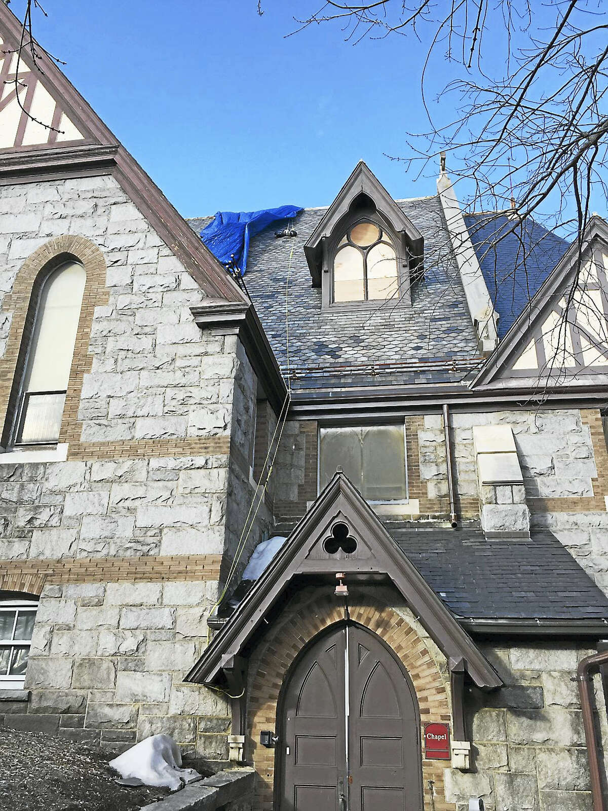 Trinity Episcopal Church seen from Water Street in Torrington, with plywood covering the windows that are being repaired.