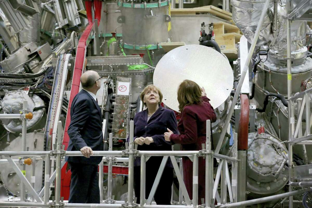 German Chancellor Angela Merkel , cemter, listens to scientific director of the Max Planck Institute for Plasma Physics, Sibylle Guenter, right, as Mecklenburg-Western Pomerania governor Erwin Sellering, left, looks on, after the plant created plasma from hydrogen for the first time at the Wendelstein 7-X nuclear fusion research centre in Greifswald, Germany, Wednesday Feb. 3, 2016. Scientists flipped the switch Wednesday on an experiment they hope will advance the quest for nuclear fusion, considered a clean and safe form of nuclear power.