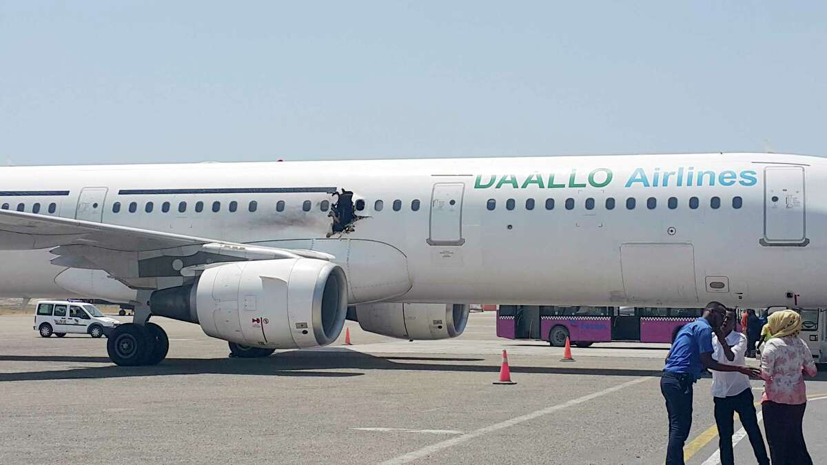 In this photo taken Tuesday, Feb. 2, 2016, a hole is seen in a plane operated by Daallo Airlines as it sits on the runway of the airport in Mogadishu, Somalia. A gaping hole in the commercial airliner forced it to make an emergency landing at Mogadishu's international airport late Tuesday officials and witnesses said.