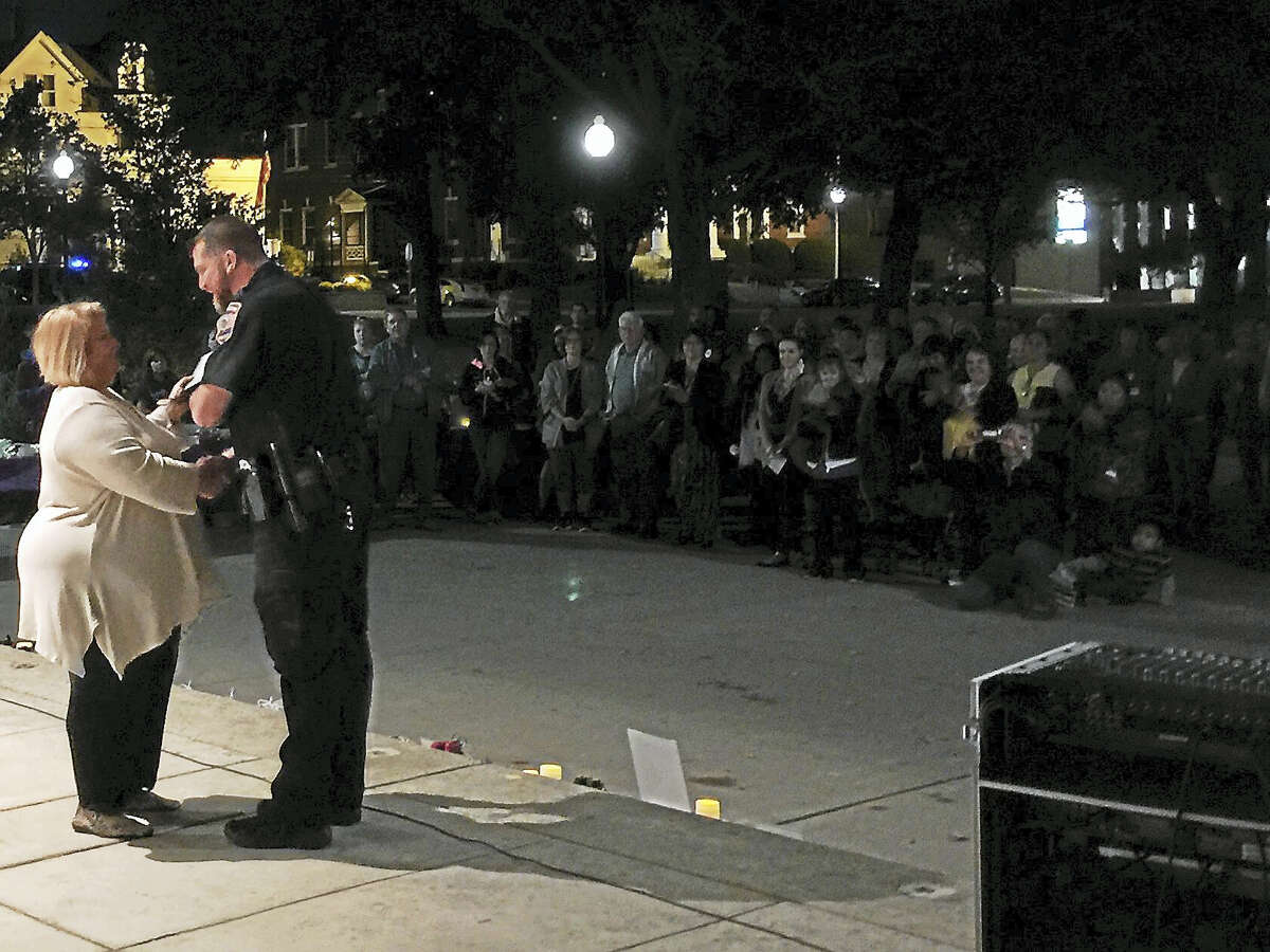 Ben Lambert - The Register CitizenA member of the Susan B. Anthony Project presents an award to Torrington Police Officer Michael Giordano during Wednesday night's 28th annual domestic violence awareness vigil at Coe Memorial Park.