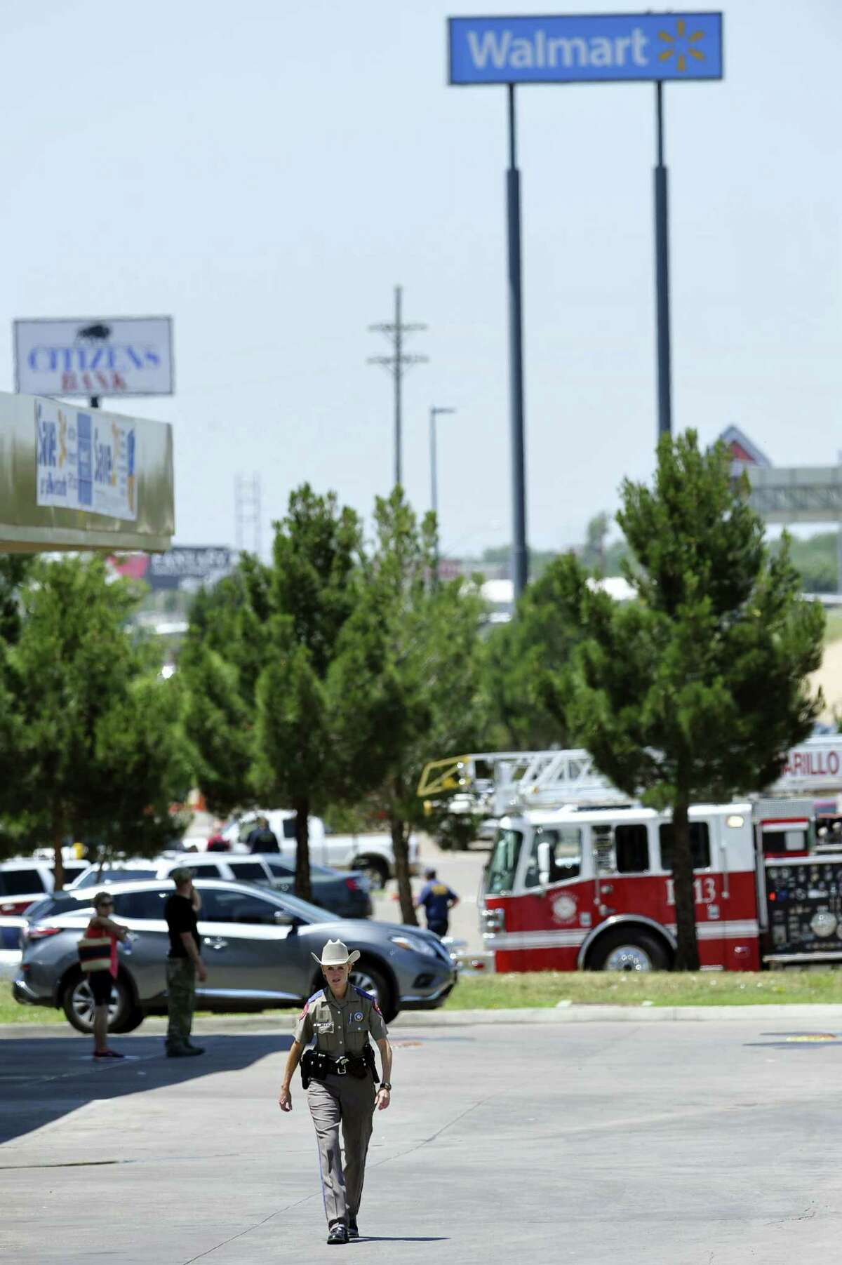 A police officer walks near a Wal-Mart store where officers responded to a reported shooting, Tuesday, June 14, 2016, in Amarillo, Texas.