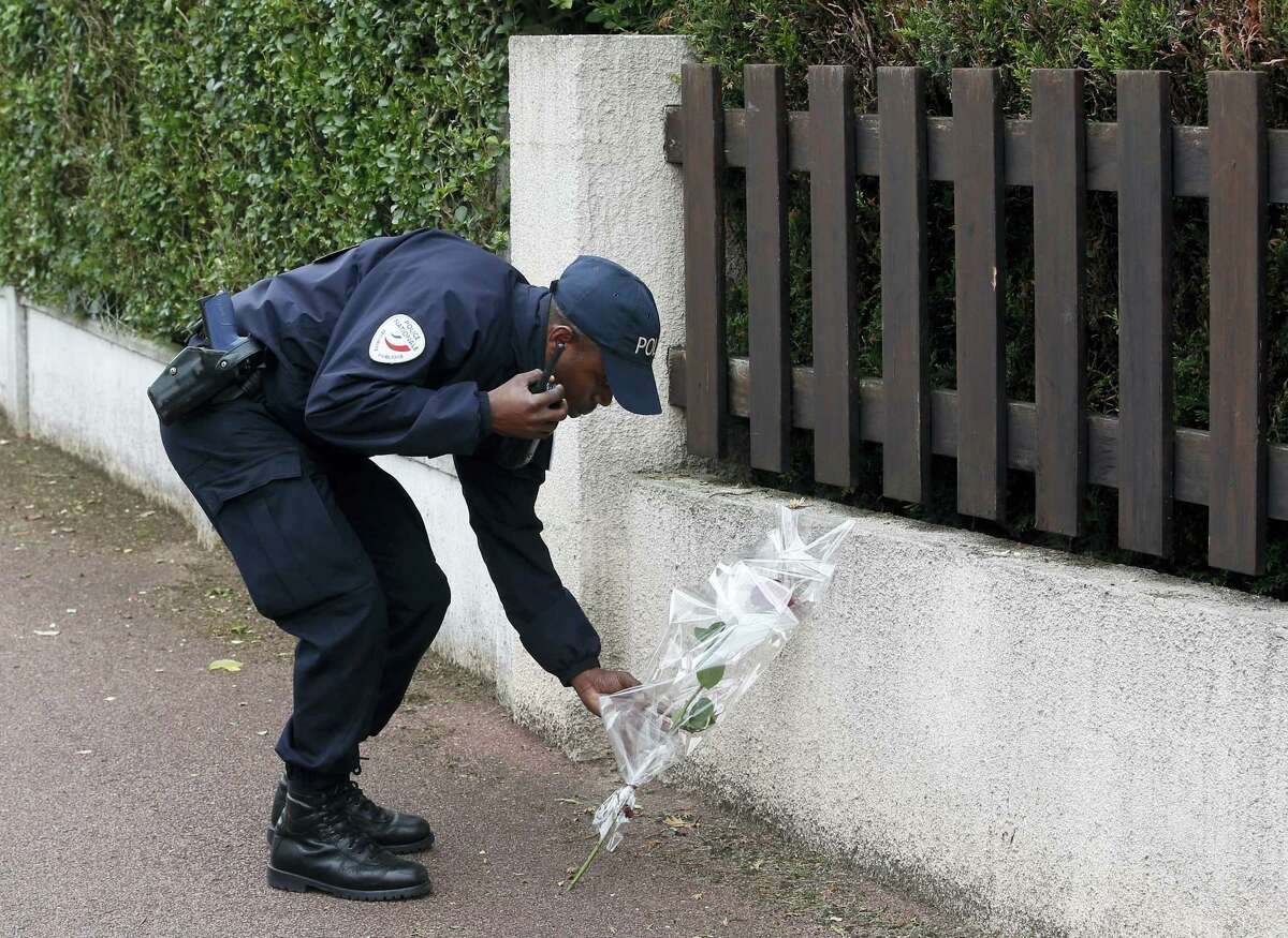 """A French police officer lays flowers while paying tribute to his colleagues killed in a knife attack near their home in Magnanville, west of Paris, France, Tuesday, June 14, 2016. French President Francois Hollande says the stabbing attack that left two police officials dead was """"incontestably a terrorist act."""""""