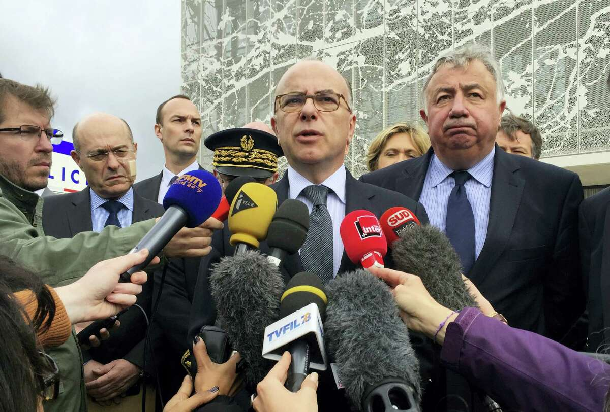French Interior Minister Bernard Cazeneuve answers reporters after visiting the police station in Les Mureaux, west of Paris, Tuesday, June 14, 2016. A 25-year-old Frenchman with a past terrorist conviction is suspected in Monday's killing of two police officials in the Paris suburb of Magnanville.