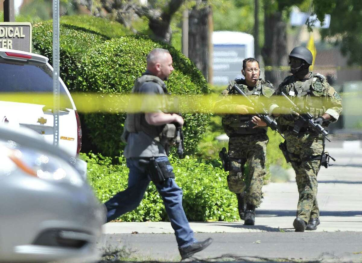 Police SWAT members move to take position at the scene of a shooting at a medical clinic Tuesday, March 31, 2015, in Fresno, Calif. A man and a woman were found dead after a shooting at the Eye Medical Clinic in downtown Fresno, police in central California said.