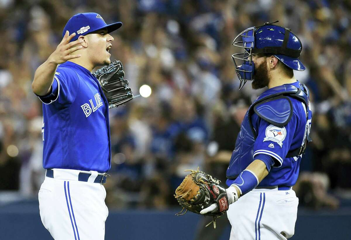 Blue Jays relief pitcher Roberto Osuna, left, and catcher Russell Martin celebrate Tuesday's win over the Indians.