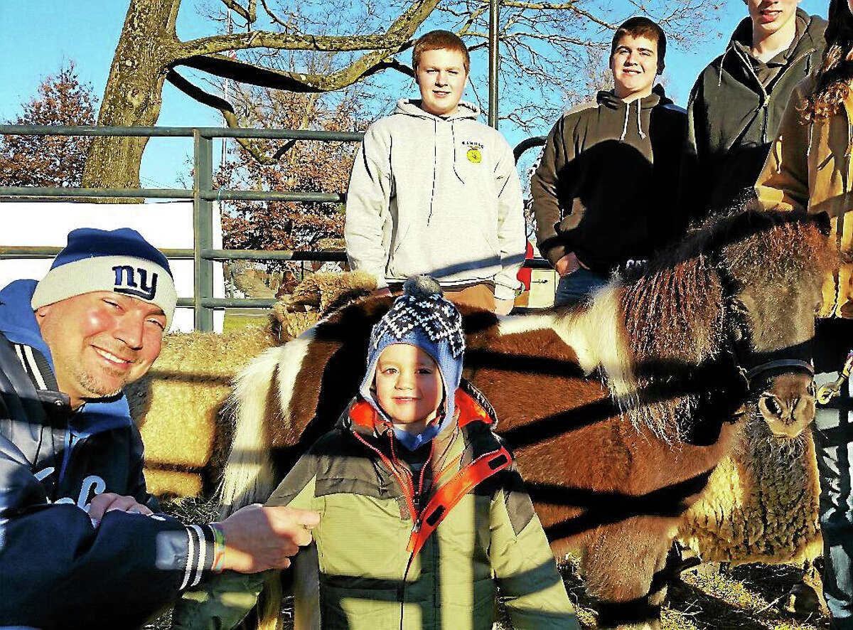 N.F. Ambery Foreground, Mike Deleppo of Litchfield and his son, Aurelian, 1 year old, met Libby, an 8-year-old miniature horse, at Wamogo Regional High School's Future Farmers of America's petting zoo at the Litchfield Town Green.