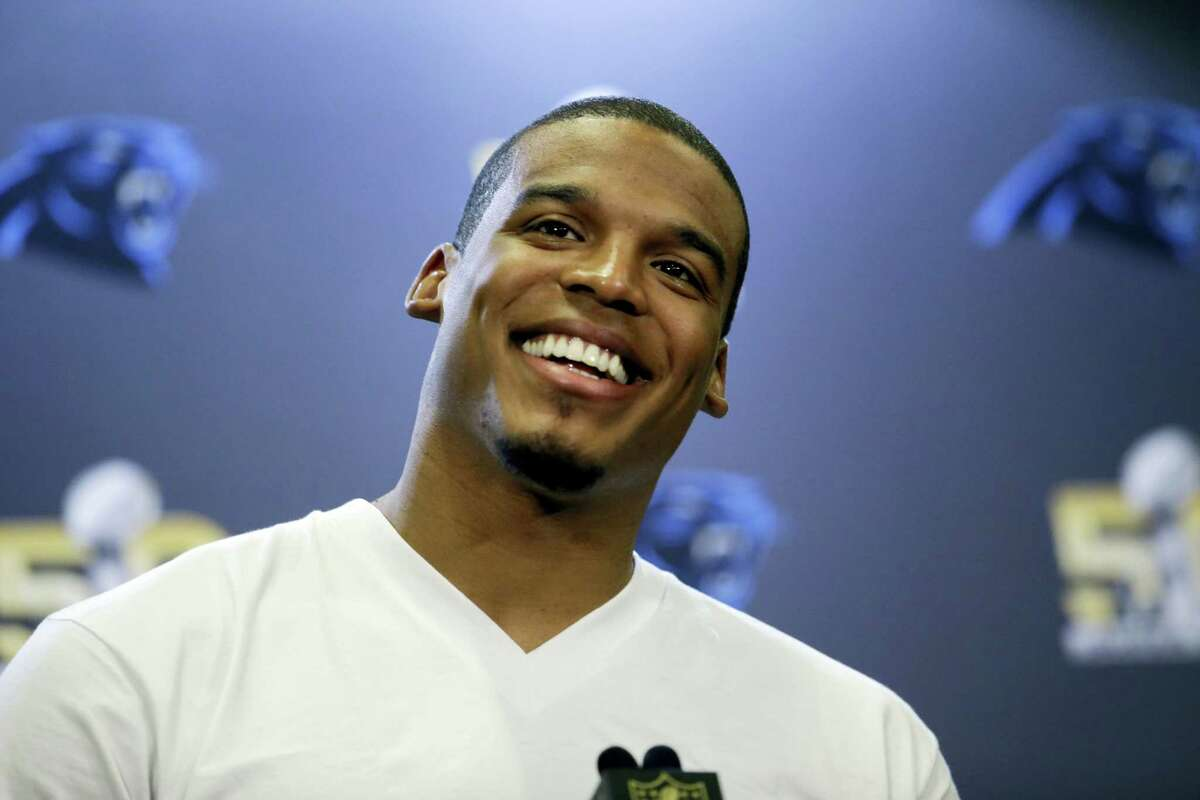 Panthers quarterback Cam Newton smiles as he answers questions during a press conference Tuesday.