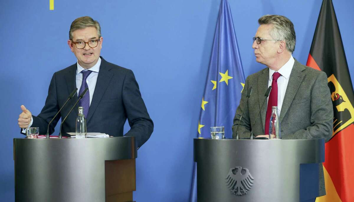 German Interior Minister Thomas de Maiziere, right, and British EU security commissioner Julian King answer journalists' questions after their meeting in Berlin, Germany, Tuesday Oct. 18, 2016.