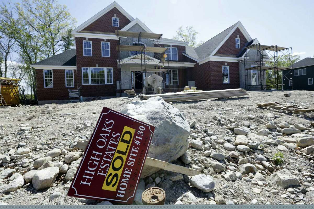 """In this May 18, 2016 photo, a """"Sold"""" sign rests in front of a house under construction, in Walpole, Mass. On Oct. 18, 2016, the National Association of Home Builders/Wells Fargo releases its October index of builder sentiment."""