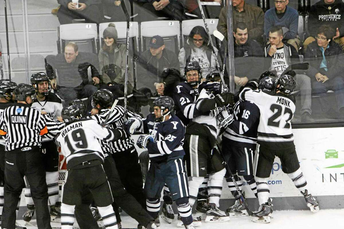 Members of the Yale and Providence hockey teams scuffle after the end of the second period on Saturday.