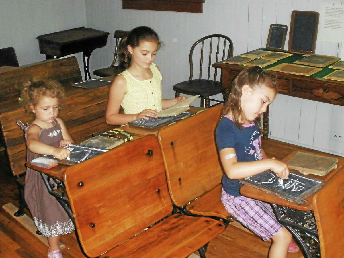 Ashley Lauer, 3, Haley Lauer, 9, and Katelyn Lauer, 5, write on slate at the Barkhamsted Historical Society's Center Schoolhouse on Sunday.
