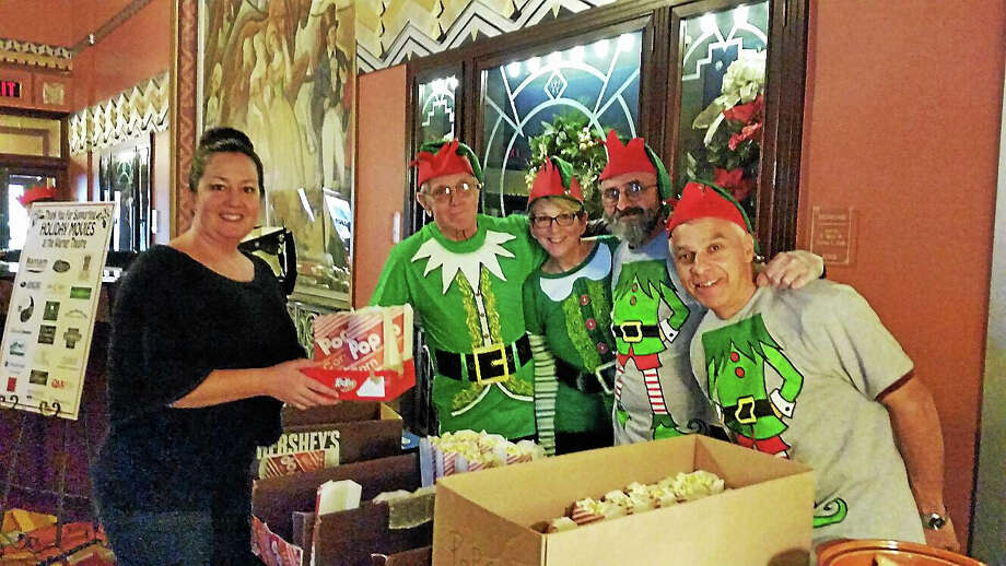 """Customer Dana Quinn of Thomaston bought popcorn from Santa's elves, Warner Theatre volunteers Joe Bonetti of Torrington; Cindy Young of Harwinton; Mike Gardinello of Torrington; and Bob Lacko of Torrington at the theater's third annual Holiday Movie Event, which included greetings by Santa and Mrs. Claus and a free screening of two classic holiday films """"The Year Without a Santa Claus"""" and """"Miracle on 34th Street."""" Photo: NF Ambery — The Register Citizen"""