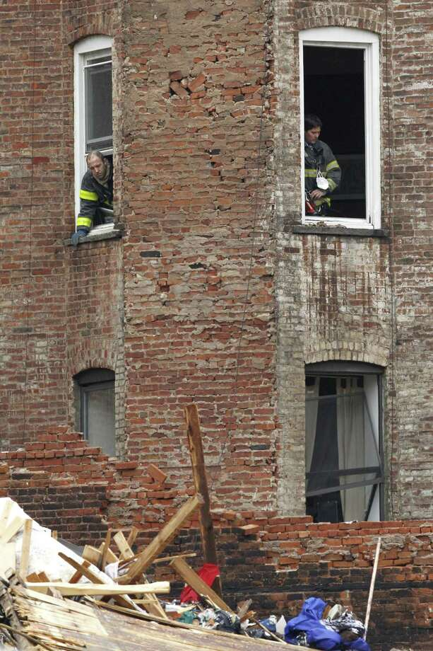 Fire officials stand at the windows of a building adjacent to the site of a building collapse in the East Village neighborhood of New York, Friday, March 27, 2015.  Nineteen people were injured, four critically, after the powerful blast and fire sent flames soaring and debris flying Thursday afternoon.  Preliminary evidence suggested that a gas explosion amid plumbing and gas work inside the building was to blame. Photo: (AP Photo/Julio Cortez) / AP