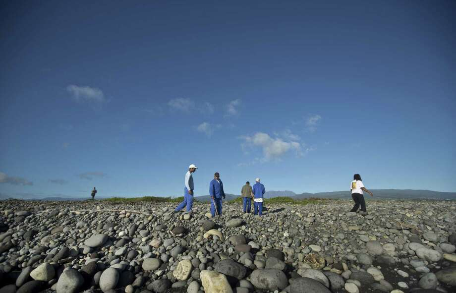 Workers for an association responsible for maintaining paths to the beaches from being overgrown by shrubs, search the beach for possible additional airplane debris near the area where an airplane wing part was washed up, in the early morning near to Saint-Andre on the north coast of the Indian Ocean island of Reunion Friday. Photo: AP Photo/Ben Curtis / AP