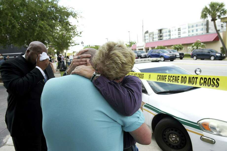 Terry DeCarlo, executive director of the LGBT Center of Central Florida, center, is comforted by Orlando City Commissioner Patty Sheehan, right, after a shooting involving multiple fatalities at a nightclub in Orlando, Fla., Sunday, June 12, 2016. (AP Photo/Phelan M. Ebenhack) Photo: AP / FR121174 AP