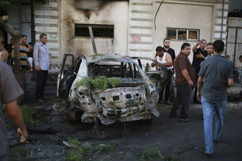 Palestinians stand around a vehicle destroyed in the blast in Gaza City on July 19, 2015. Photo: AP Photo/Ali Hassan / AP