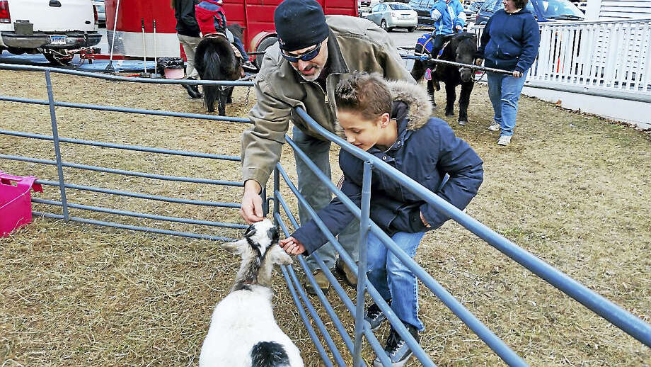 Jim Meyers and his son Mitchell, 11, both of Torrington, met a goat at the petting zoo at the eighth Annual Winter Carnival at Major Besse Park near the First Congregational Church in Torrington this weekend. Photo: NF AMBERY — REGISTER CITIZEN
