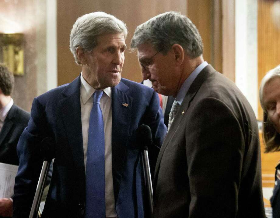 Secretary of State John Kerry talks with Senate Armed Services Committee member Sen. Joe Manchin, D-W.Va., on Capitol Hill in Washington on Wednesday. Photo: AP Photo  / AP