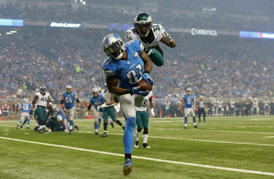 Detroit Lions receiver Calvin Johnson, defended by Philadelphia Eagles cornerback Eric Rowe, scores one of his three touchdowns on Thursday. Photo: Paul Sancya — The Associated Press  / AP