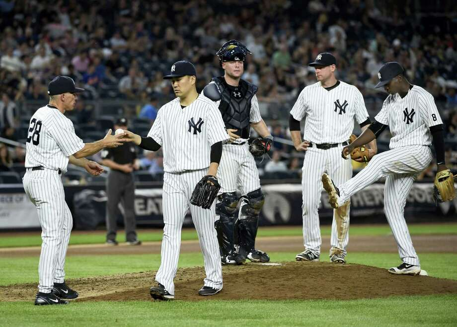 Yankees manager Joe Girardi takes the ball from starting pitcher Masahiro Tanaka during Saturday's game. Photo: Kathy Kmonicek — The Associated Press  / FR170189 AP