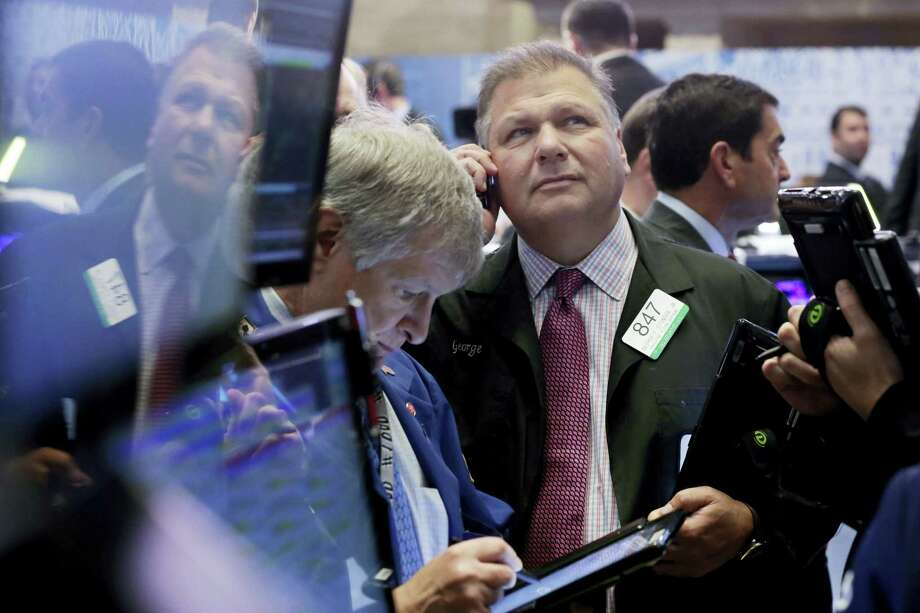 Trader George Ettinger, center, works on the floor of the New York Stock Exchange Monday. Photo: Richard Drew — The Associated Press  / AP