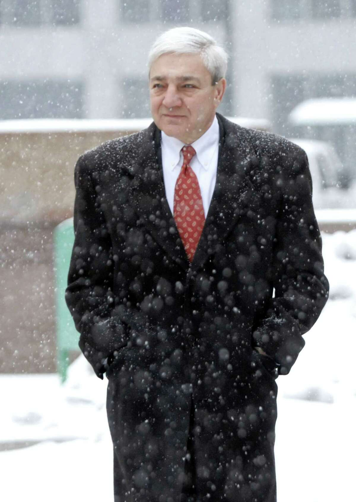 Former Penn State President Graham Spanier walks to the Dauphin County Court in a snow storm for a pretrial hearing in Harrisburg, Pa. on Tuesday, Dec. 17, 2013.