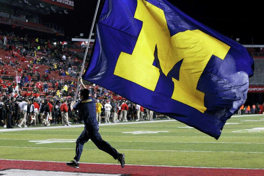A Michigan flag bearer celebrates a touchdown during a recent game. Photo: Mel Evans — The Associated Press  / AP
