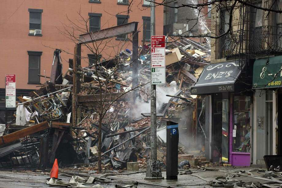 Debris from collapsed buildings smolders in the East Village neighborhood of New York, Friday, March 27, 2015. Authorities say two people are unaccounted for following an apparent gas explosion that leveled three buildings.  Preliminary evidence suggested a gas explosion amid plumbing and gas work inside the building was to blame.  (AP Photo/Mark Lennihan) Photo: AP / AP