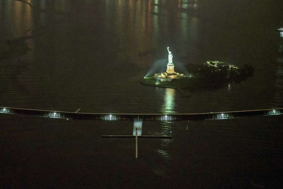 In this photo released by Jean Revillard/ SI2, solar-powered airplane Solar Impulse 2, piloted by Swiss adventurer Andre Borschberg, flies over the Statue of Liberty in New York Saturday, June 11, 2016, shortly before landing at John F. Kennedy International Airport. The Swiss-made Solar Impulse 2 has landed in New York City on the latest leg of its globe-circling voyage. It had left Lehigh Valley International Airport in Pennsylvania late Friday. Photo: Jean Revillard/ SI2 Via AP   / Jean Revillard/ SI2