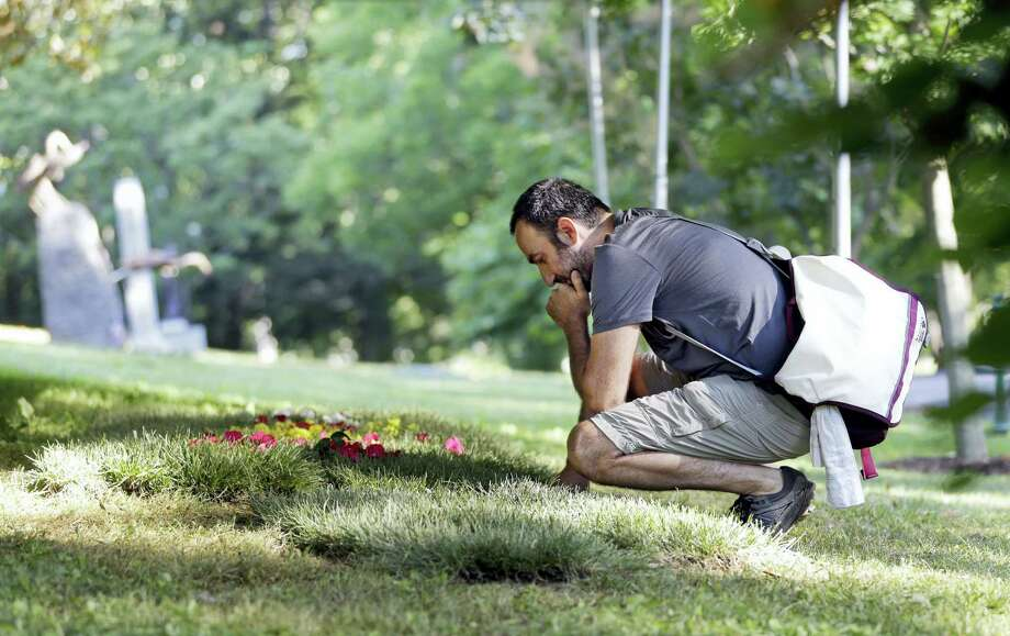 Arzam Farrokhi, an Iranian native now living in New York, visits the grave of boxing great Muhammad Ali, Saturday, June 11, 2016, in Louisville, Ky. Cave Hill Cemetery opened to the public Saturday, the day after Ali's burial. Photo: AP Photo/Mark Humphrey   / Copyright 2016 The Associated Press. All rights reserved. This material may not be published, broadcast, rewritten or redistribu