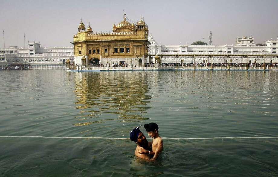 In this April 13, 2013, file photo, a Sikh man holds a child as they take a holy dip in the sacred pond at the Golden Temple, Sikhs holiest shrine, during Baisakhi festival in Amritsar, India. The chronic air pollution blanketing much of northern India is now threatening the holiest shrine in the Sikh religion, making the once-gleaming walls of the Golden Temple dingy and dull. Photo: AP Photo/Sanjeev Syal, File   / AP