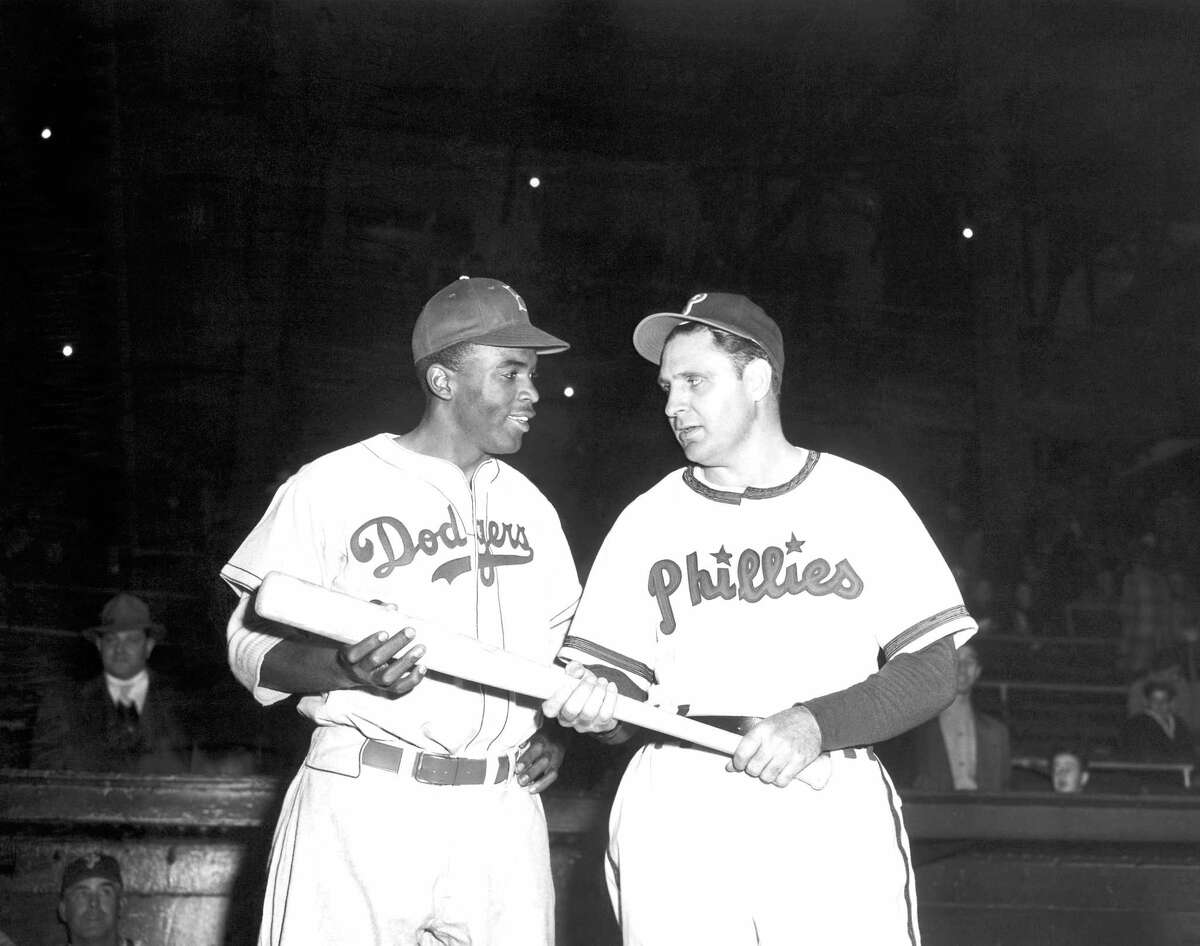 In a May 9, 1947, file photo, Jackie Robinson, left, Brooklyn Dodgers' first baseman, looks over the bat Philadelphia Phillies manager Ben Chapman uses during practice, as he prepared to play his first Philadelphia game for the Dodgers. The Philadelphia City Council unanimously passed a resolution Thursday, March 31, 2016, naming April 15, 2016, as a day to honor Robinson's achievements and to apologize for the racism he faced while visiting Philadelphia in 1947. Robinson was refused service by a local hotel and then taunted by Philadelphia Phillies manager Ben Chapman, who, along with players, mercilessly hurled racial slurs at Robinson each time he came to bat.