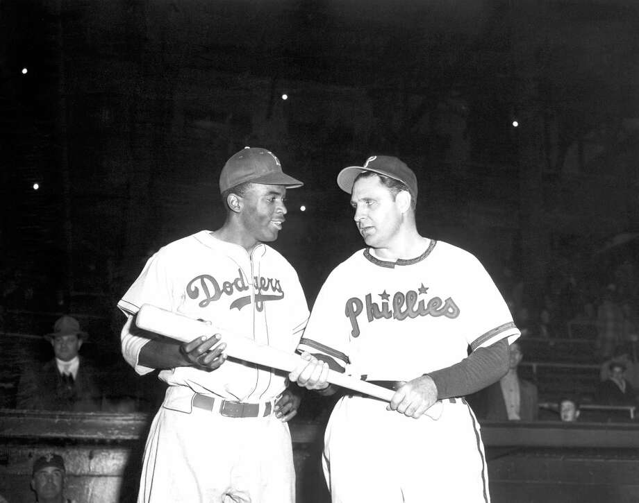In a May 9, 1947, file photo, Jackie Robinson, left, Brooklyn Dodgers' first baseman, looks over the bat Philadelphia Phillies manager Ben Chapman uses during practice, as he prepared to play his first Philadelphia game for the Dodgers. The Philadelphia City Council unanimously passed a resolution Thursday, March 31, 2016, naming April 15, 2016, as a day to honor Robinson's achievements and to apologize for the racism he faced while visiting Philadelphia in 1947. Robinson was refused service by a local hotel and then taunted by Philadelphia Phillies manager Ben Chapman, who, along with players, mercilessly hurled racial slurs at Robinson each time he came to bat. Photo: AP Photo, File   / AP