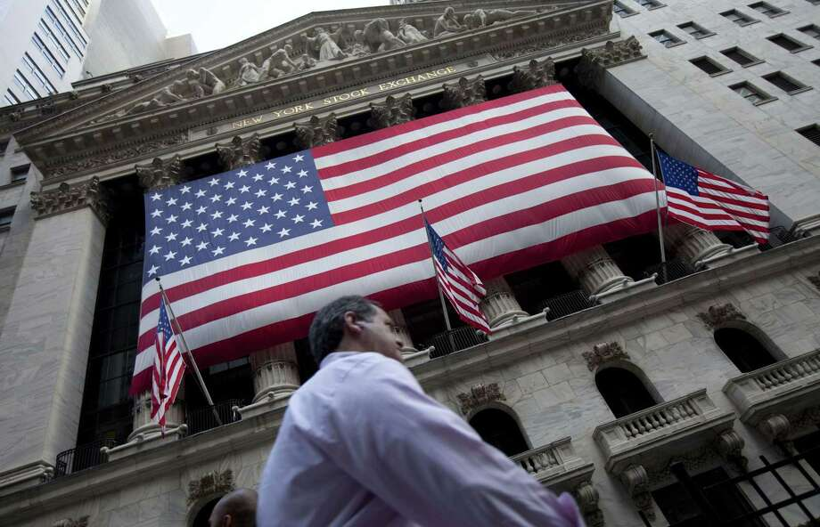 A pedestrian walks past the New York Stock Exchange in New York. Photo: Jin Lee — The Associated Press  / FR159730 AP