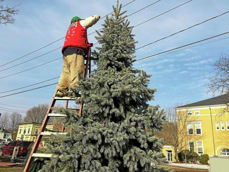 Tim Wheeler helps take down the holiday lights in Winsted on Friday. Photo: Ben Lambert — The Register Citizen