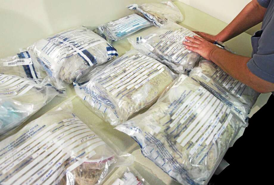 A Cleveland police officer looks over bags of heroin at a news conference in Cleveland, Ohio. Photo: AP Photo/Amy Sancetta, File  / AP2010
