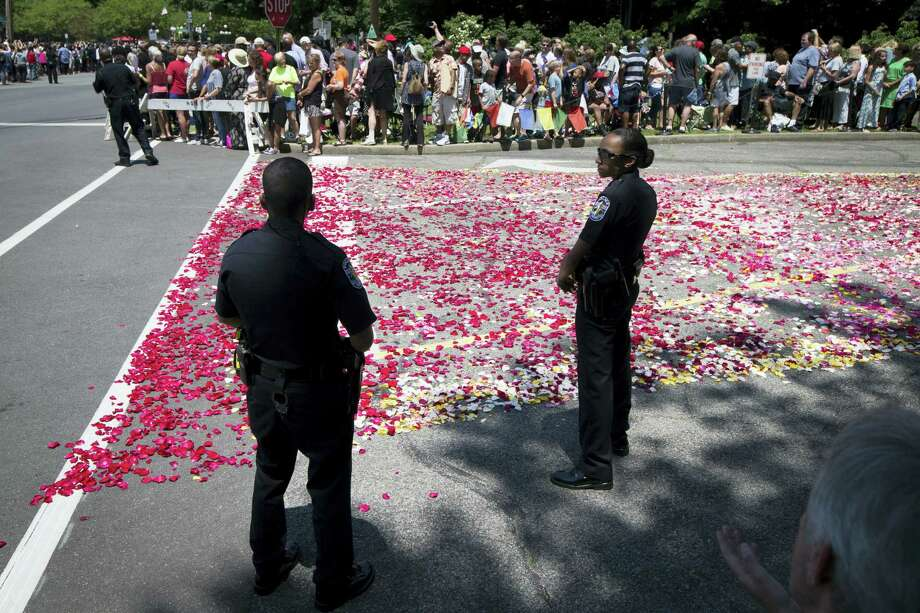 Police stand guard along a rose petal-covered entrance way to Cave Hill Cemetery before the arrival of Muhammad Ali's funeral procession, Friday, June 10, 2016, in Louisville, Ky. Ali's body rode in a miles-long procession spanning his life — from his boyhood home where he shadowboxed and dreamed of greatness to the boulevard that bears his name and the museum that stands as a lasting tribute to his boxing triumphs and his humanitarian causes outside the ring. Ali died last Friday at 74 after a long battle with Parkinson's disease. Photo: AP Photo — John Minchillo   / AP