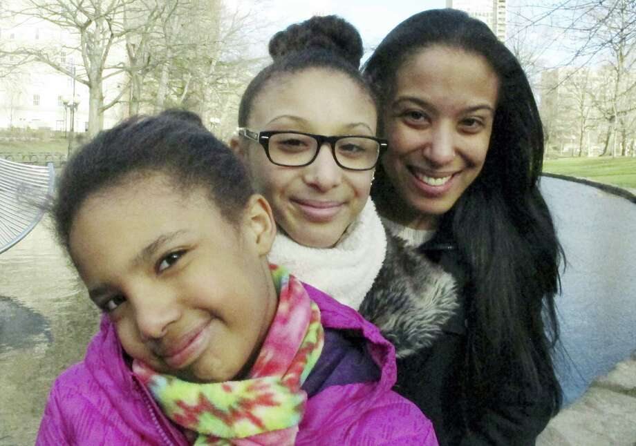 In this March 21, 2016 photo, Adelaida Torres, right, poses with daughters Elizabeth, left, and Gloria, center, in Hartford, Conn. Torres believes she never would have won custody of her two daughters in 2013 during a bitter court fight with her now-ex-husband if not for the free legal help from attorney Linda Allard and Greater Hartford Legal Aid. Connecticut lawmakers are considering a bill that would create a task force to look into expanding the right to free lawyers for the poor in civil cases. Photo: AP Photo/Dave Collins  / AP