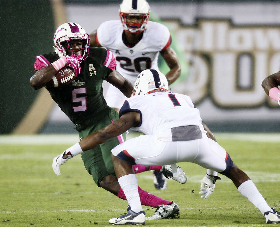 South Florida running back Marlon Mack (5) tries to avoid a tackle by UConn cornerback John Green in the first quarter on Saturday. Photo: Octavio Jones — Tampa Bay Times Via AP  / Tampa Bay Times