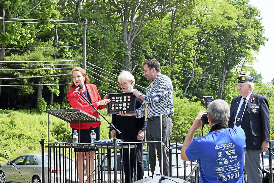 """Congressman Elizabeth Esty, left, presents medals to Margaret """"Maggie"""" Klein, widow of Irwin Klein, during a ceremony at the All-Wars Memorial in Bantam on Saturday, June 4. Photo: Contributed Photos"""
