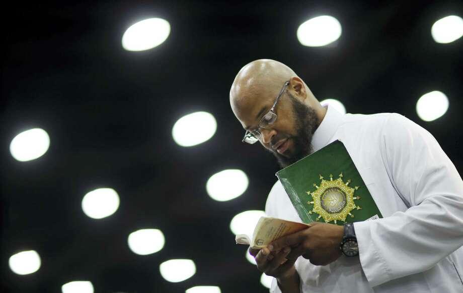 Saayfullaah Ali reads prayers before Muhammad Ali's Jenazah, a traditional Islamic Muslim service, in Freedom Hall on June 9, 2016, in Louisville, Ky. Photo: AP Photo — David Goldman  / AP