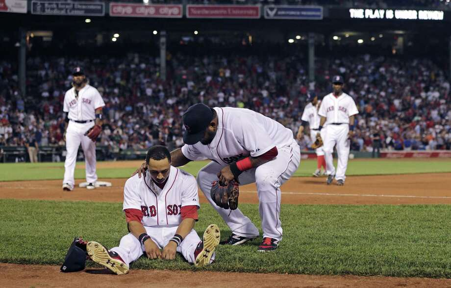 Boston Red Sox center fielder Mookie Betts sits on the infield as teammate Pablo Sandoval checks to see if he's injured following a play where Betts flipped over the bullpen wall while trying to catch a drive by Chicago White Sox's Jose Abreu during the sixth inning of a baseball game at Fenway Park in Boston, Tuesday, July 28, 2015.  Betts left the game after the play. Photo: Charles Krupa — The Associated Press  / AP