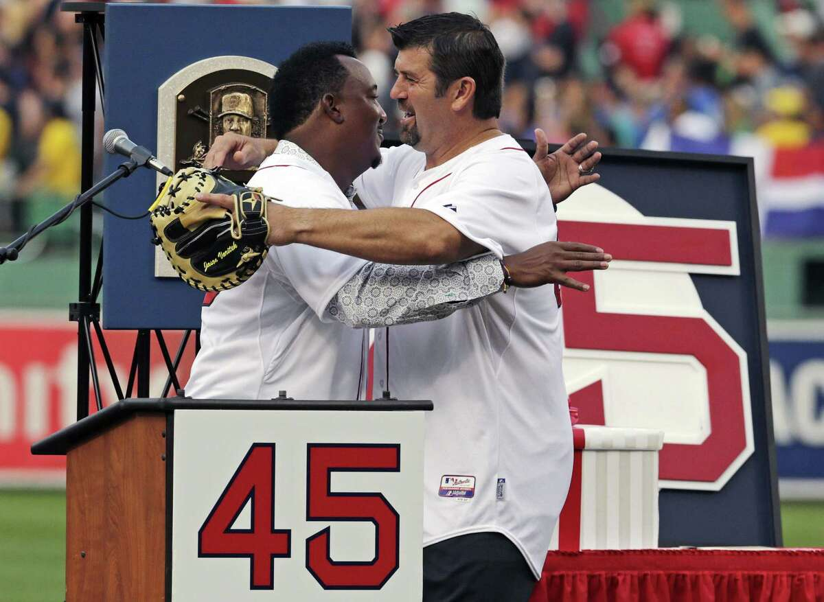 Baseball Hall of Fame member and former Boston Red Sox player Pedro Martinez, left, is embraced by teammate Jason Varitek after his jersey was retired prior to a game against the Chicago White Sox at Fenway Park in Boston Tuesday. AP Photo/Charles Krupa)