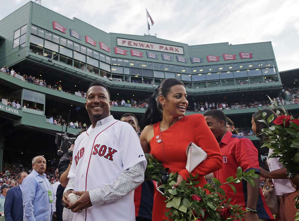 Pedro Martinez, left, walks off the field with his wife, Carolina, during a ceremony where his jersey was retired.