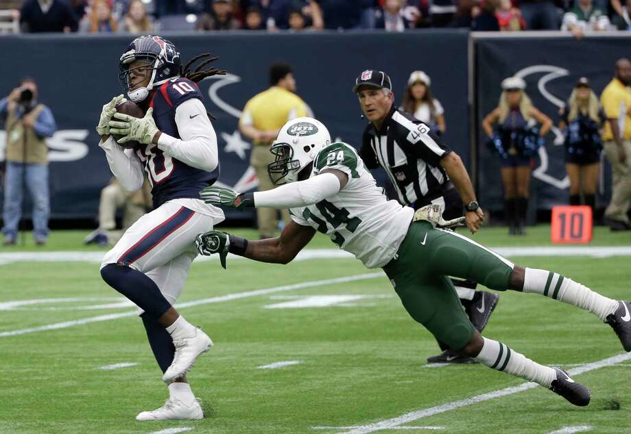 Houston Texans receiver DeAndre Hopkins pulls in a pass for a touchdown by New York Jets cornerback Darrelle Revis on Sunday. Photo: David J. Phillip — The Associated Press  / AP